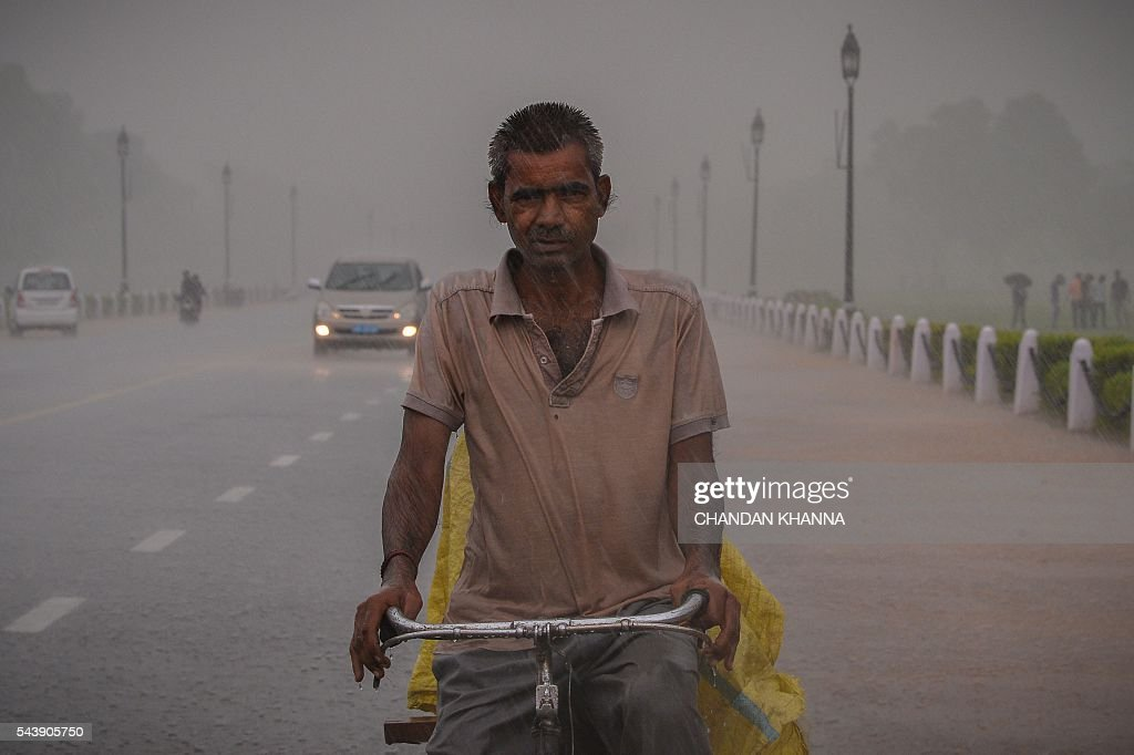 An Indian labourer rides his bicycle through a heavy monsoon rainshower in New Delhi on June 30, 2016. / AFP / CHANDAN