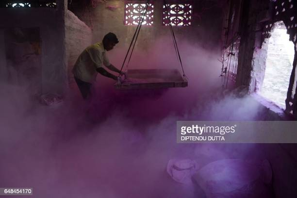 TOPSHOT An Indian labourer sifts coloured powder known as 'gulal' to be used during the forthcoming spring festival of Holi inside a factory at...