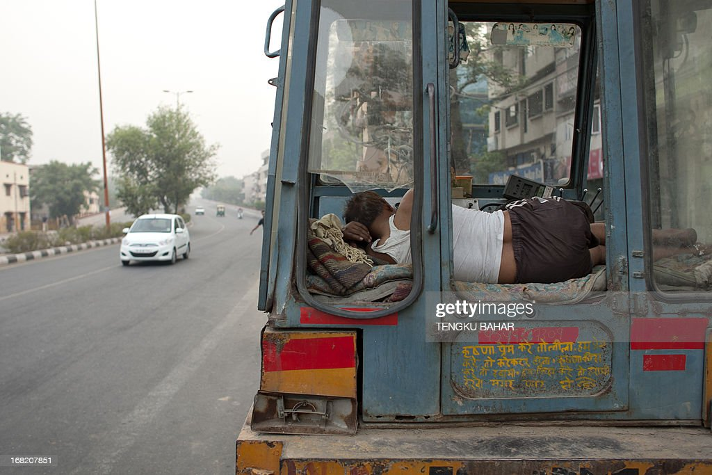 An Indian labourer sleeps in the operator's compartment of an excavating machine parked on the roadside in New Delhi on May 7, 2013. According to the World Bank, India has a gross national income per capita of 1,410 US Dollars (USD), against 780 USD in Bangladesh and 540 USD in Nepal. AFP PHOTO/TENGKU BAHAR