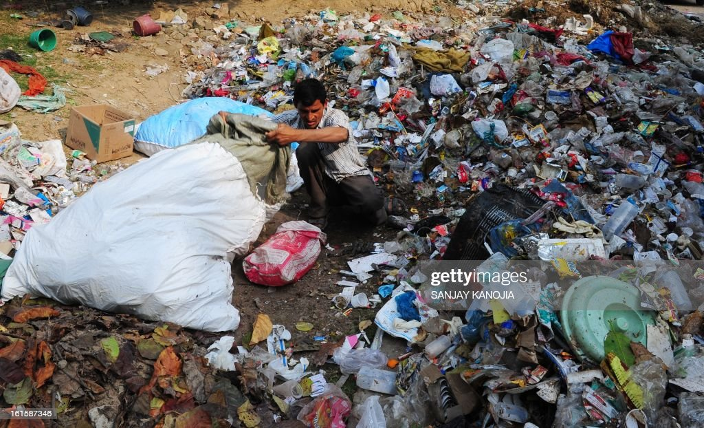 An Indian labourer sorts through garbage in search of recyclable materials in Allahabad on February 12, 2013. To help clean up the Kumbh Mela festival more than 10,000 street sweepers are on hand, ready to pick up as much as 50 tons of trash every day. AFP PHOTO/ SANJAY KANOJIA