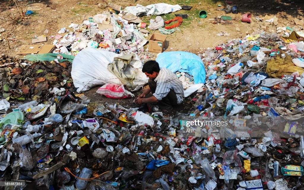 An Indian labourer sorts through garbage in search of recyclable materials in Allahabad on February 12, 2013. To help clean up the Kumbh Mela festival more than 10,000 street sweepers are on hand, ready to pick up as much as 50 tons of trash every day.