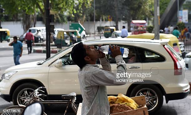 An Indian labourer takes a break as he drinks water to get respite from heat in New Delhi on May 26 2015 At least 800 people have died in a major...