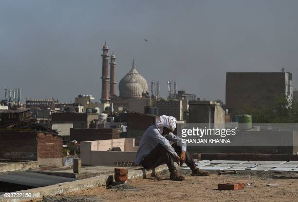 An Indian labourer takes a break from work as he sits on a rooftop in Kinari Bazar a busy market in the Chandni Chowk area of New Delhi on June 8...