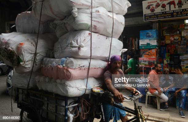 An Indian labourer uses a rickshaw transport material through the main wholesale market area of the city in Kolkata on May 31 2017 India's economic...