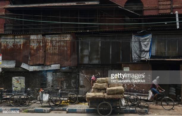 TOPSHOT An Indian labourer uses a rickshaw transport material through the main wholesale market area of the city in Kolkata on May 31 2017 India's...
