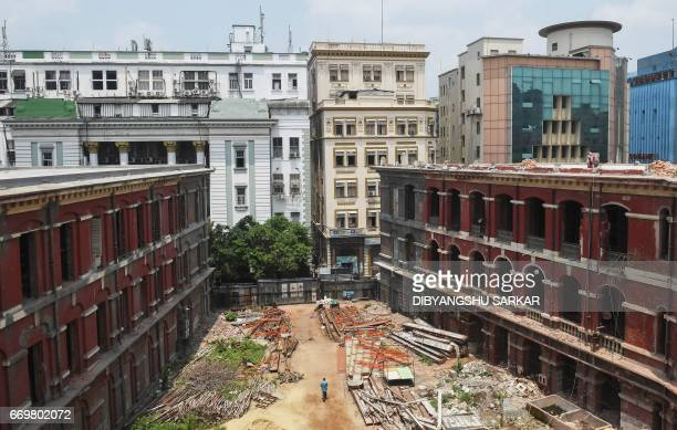 An Indian labourer walks by the underrenovation historic Writers' Building in Kolkata on World Heritage Day on April 18 2017 The redbrick complex...