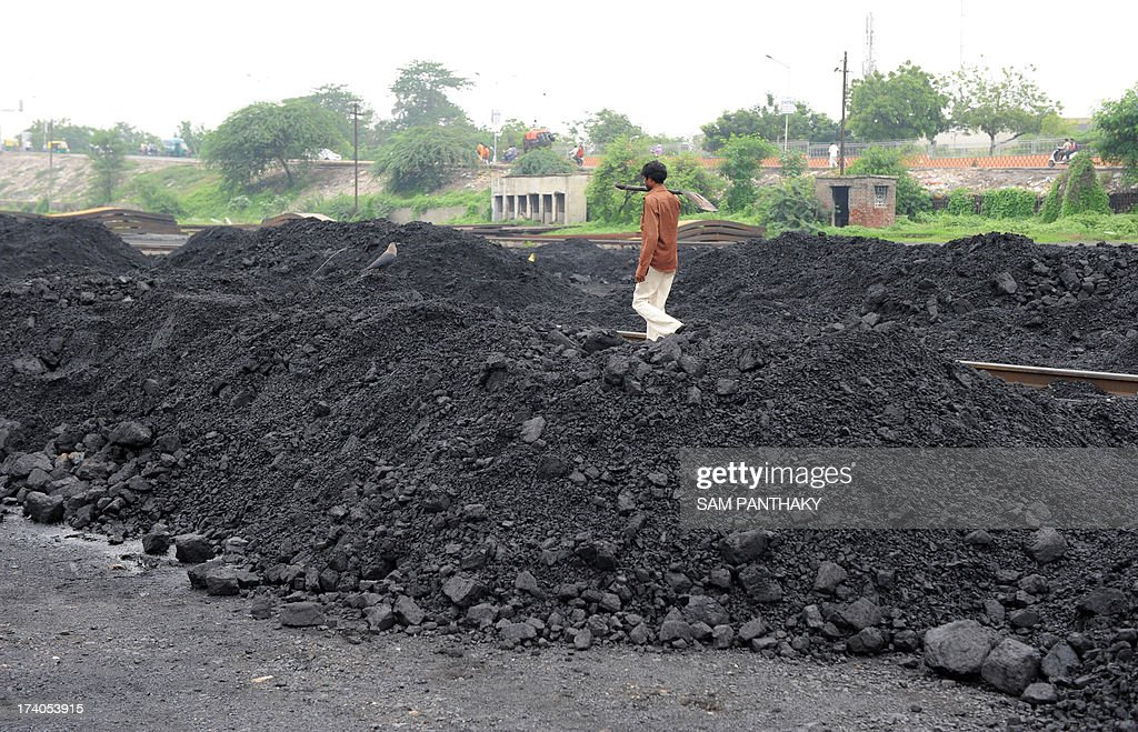 An Indian labourer walks past mounds of coal at the Kankaria Railway yard in Ahmedabad on July 20, 2013. In 1973, India nationalised its coal industry and created state-run giant Coal India. Then in 1993 it allowed private companies to mine coal for their own use when state output could not supply demand. AFP PHOTO/ Sam PANTHAKY