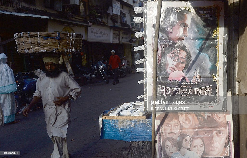An Indian labourer walks past posters of 1960 epic Indian film Mughal-E-Azam (Mughal Emperor of Emperors) displayed at a shop selling Bollywood memorabilia in Mumbai on April 30, 2013. One hundred years after the screening of a black-and-white silent film, India's brash, song-and-dance-laden Bollywood film industry celebrates its centenary later this week. The milestone will be marked with little fanfare, while India will be honoured as 'guest country' at next month's Cannes festival.