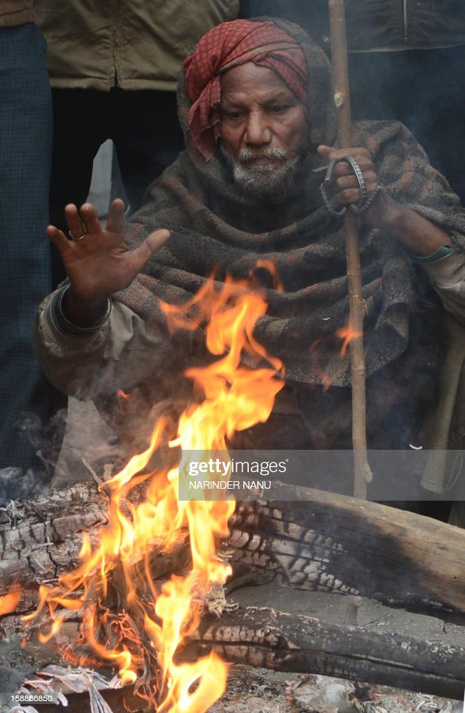 An Indian labourer warms himself by a bonfire at a roadside in Amritsar on January 2, 2013. Temperatures dropped across northern India, with the Indian capital New Delhi recording its coldest temperatures of the season.