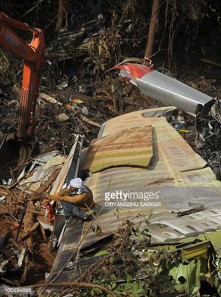 An Indian labourer working at the crash site of the doomed Air India Express flight 812 rests on a wing section of the aircraft's wreckage during...