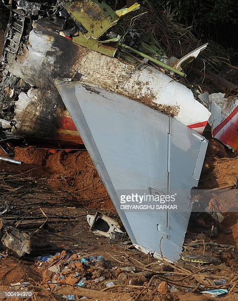 An Indian labourer working at the crash site of the doomed Air India Express flight 812 rests on a tailwing section of the aircraft's wreckage during...