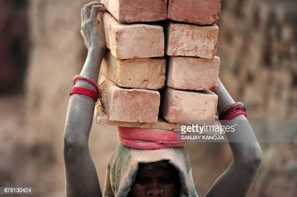 An Indian labourer works at a brick factory near Allahabad on April 30 on the eve of International Labour Day / AFP PHOTO / Sanjay KANOJIA