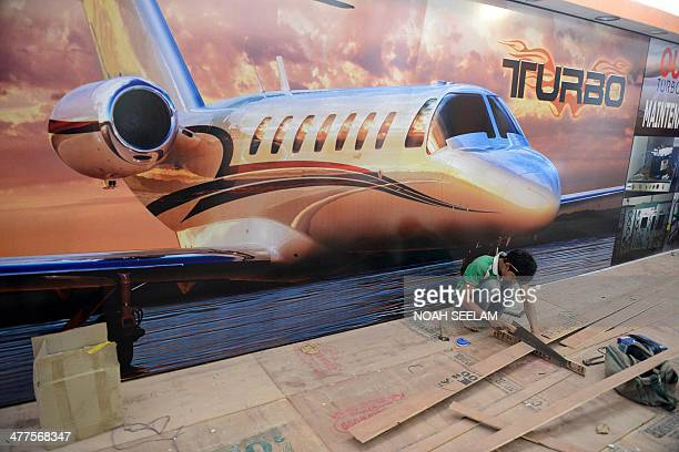 An Indian labourer works on a display stand at Begumpet Airport in Hyderabad on March 10 ahead of The India Aviation 2014 show The fourth edition of...