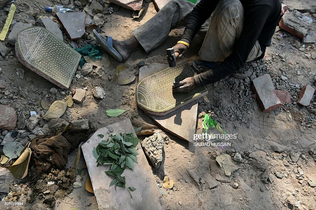 An Indian labourer works on a stone on the old quarters of New Delhi on May 1, 2016. / AFP / SAJJAD