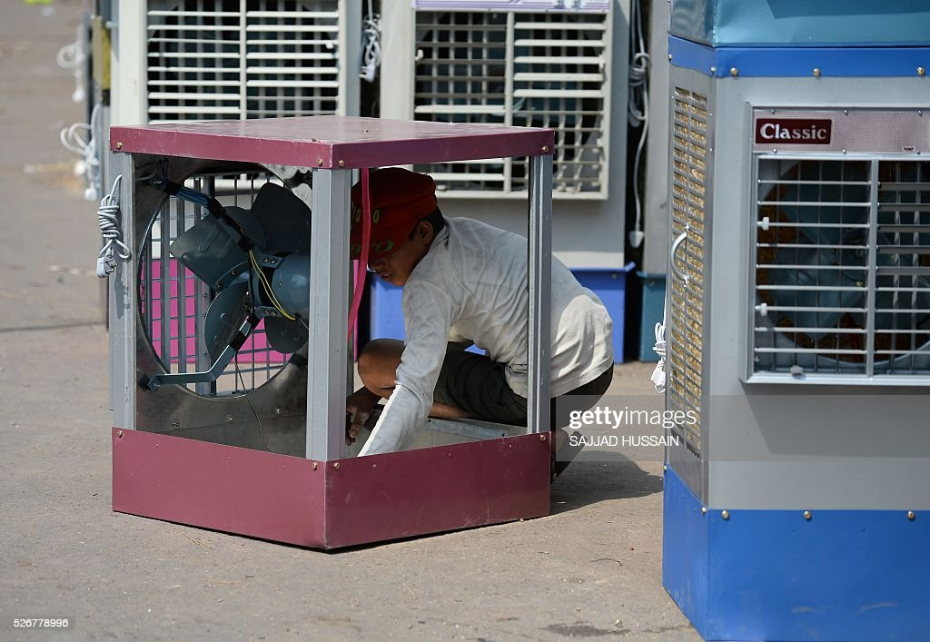 An Indian labourer works on a water cooler at a market in the old quarters of New Delhi on May 1, 2016. / AFP / SAJJAD