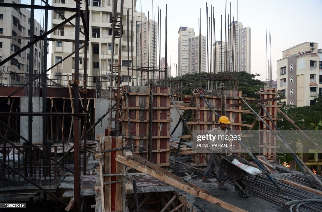 An Indian labourer works on the site of an under-construction building in Mumbai on January 23, 2013. India is experiencing galloping urbanisation, part of a global trend that has led more than half of the world's population to reside in towns and cities. AFP PHOTO/ PUNIT PARANJPE