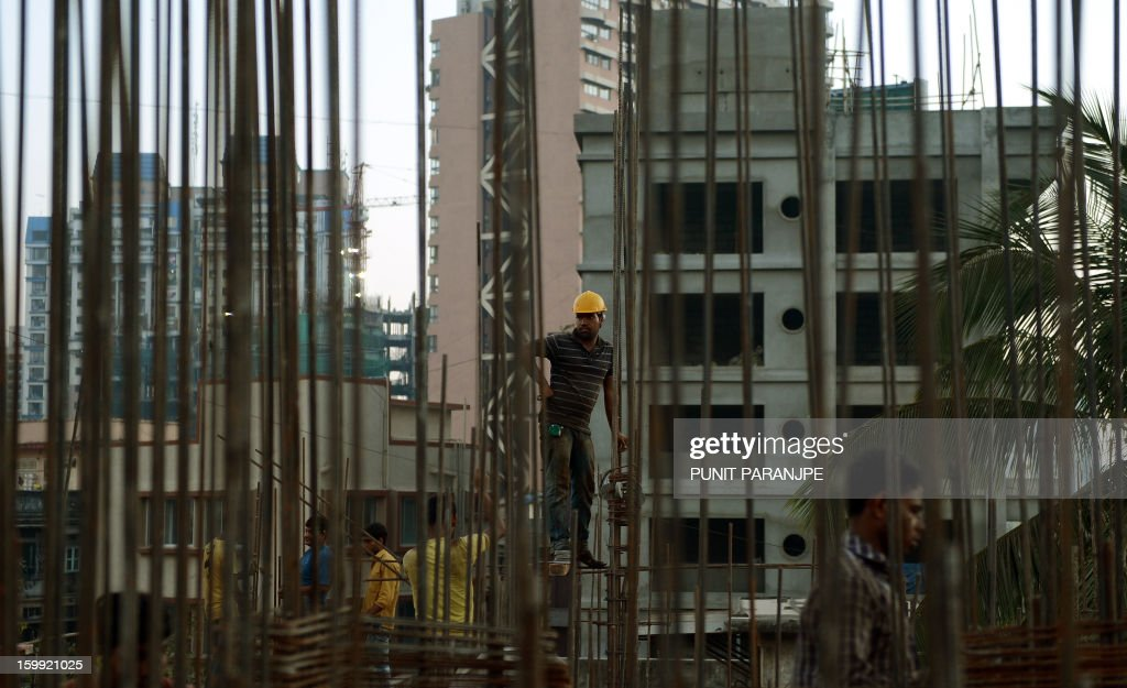 An Indian labourer works on the site of an under-construction building in Mumbai on January 23, 2013. India is experiencing galloping urbanisation, part of a global trend that has led more than half of the world's population to reside in towns and cities.