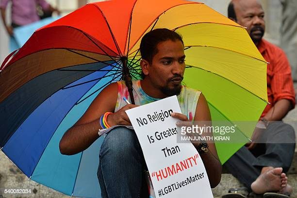 An Indian LGBT activist holds a placard during a demonstration and candlelight vigil held in Bangalore on June 14 condemning the killing of 49 people...