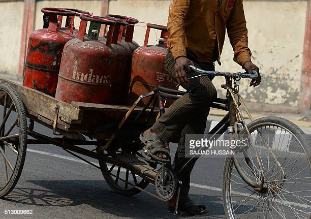 An Indian Liquid Petroleum Gas vendor carries gas cylinders on a cycle rickshaw outside a depot in New Delhi on February 29 2016 In his budget...