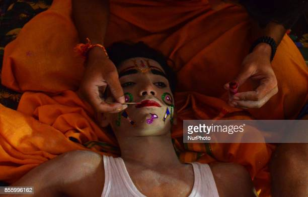 An Indian man applies make up on an artist before traditional Ramleelaa play narrating the life of Hindu God Ramon ocassion of Dussehra festivalin...