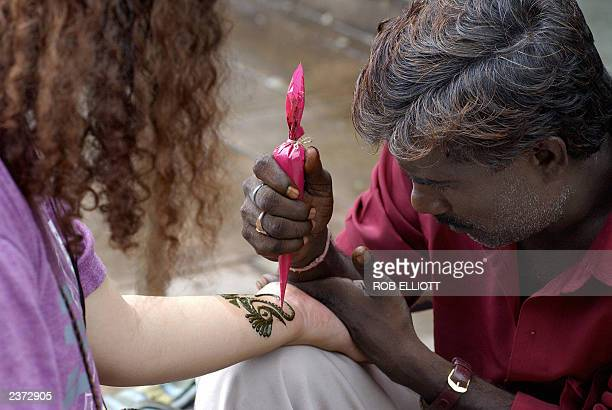 An Indian man applies the art of Mehndi to a woman's arm with a small motif for 20 Rupees near a temple complex in Janpath New Delhi 02 August 2003...