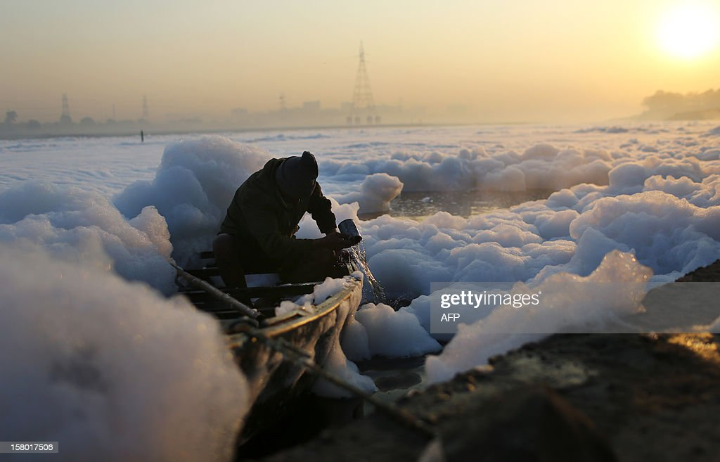 An Indian man bails water from his boat while surrounded by polluted foam in New Delhi at dawn on December 9, 2012. India's Supreme Court said on December 8, all parameters of water quality of river Yamuna indicate that it resembles a drain and urged authorities to make it pollution-free. Over 2,400 million liters of untreated sewage flows into the Yamuna every day. AFP PHOTO/ Andrew Caballero-Reynolds