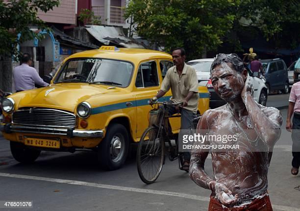 An Indian man bathes using water from a municipal water supply at the roadside in Kolkata on June 10 2015 AFP PHOTO / Dibyangshu Sarkar