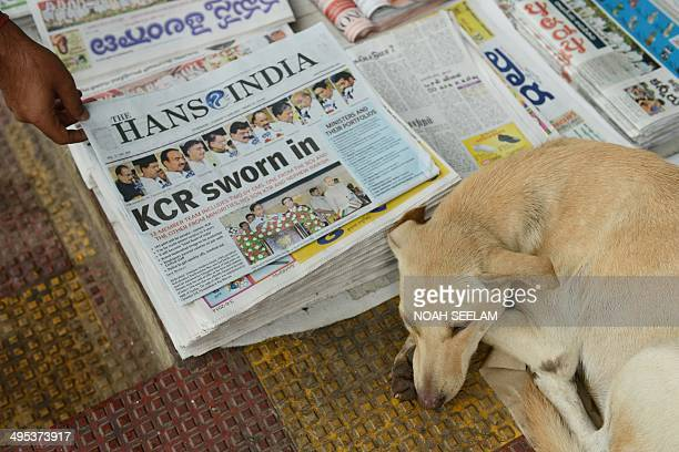 An Indian man buys a newspaper reporting on the newlyformed Telangana state's first Chief Minister K Chandra Sekhar Rao taking office in Hyderabad on...