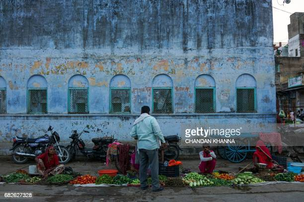 An Indian man buys vegetables from vendors at a street market in Kekri some 78 kms south of Ajmer on May 13 in the northern state of Rajasthan / AFP...