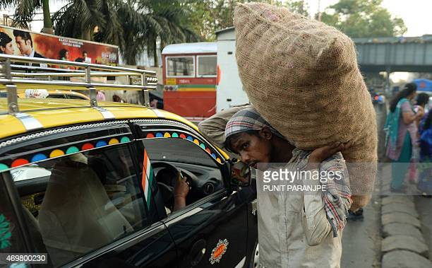 An Indian man carries a sack of onions on a busy street in Mumbai on April 15 2015 India's wholesale prices dropped for the fifth straight month in...