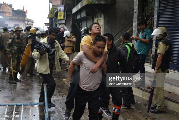 An Indian man carries another during clashes with Gorkhaland supporters during an indefinite strike called Gorkha Janamukti Morcha in Darjeeling on...