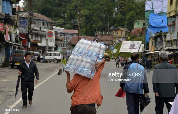 An Indian man carries bottles of drinking water during the 23th day of an indefinite strike called by separatist group Gorkha Janmukti Morcha in...