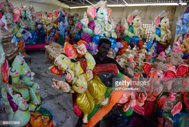 An Indian man carries finished idols of the elephantheaded Hindu deity Ganesha at a workshop ahead of the Ganesh Chaturthi festival in Chennai on...