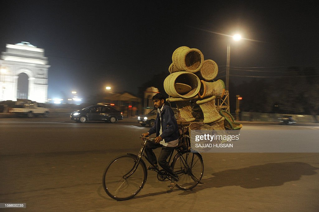 An Indian man carries furniture on his cycle as he passes in front of India Gate in New Delhi on December 20,2012. India cut its growth forecast for the current fiscal year to just under six percent in December, putting Asia's third-largest economy on track for its worst annual performance in a decade. AFP PHOTO/ SAJJAD HUSSAIN