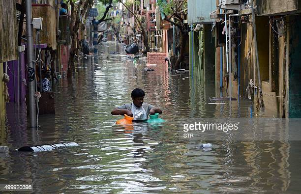 TOPSHOT An Indian man carries gas canisters through floodwaters on a street in Chennai on December 4 2015 Thousands of rescuers are racing to...