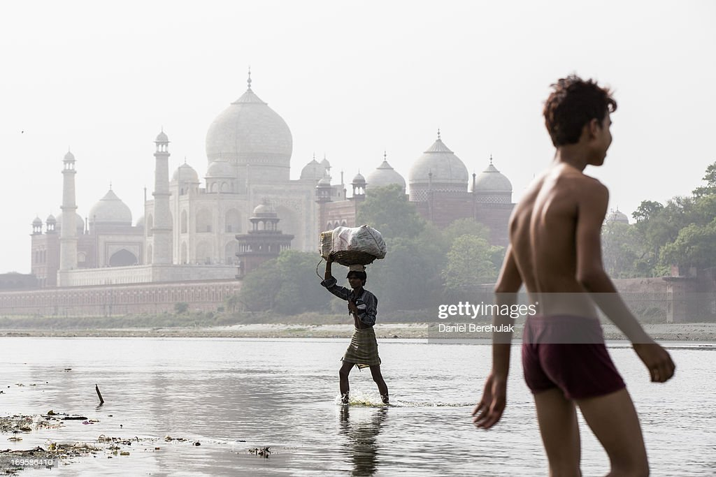 An Indian man carries goods as crosses the Yamuna river with the Taj Mahal is seen in the distance on May 28, 2013 in Agra, India. Completed in 1643, the mausoleum was built by the Mughal emperor Shah Jahan in memory of his third wife, Mumtaz Mahal, who is buried there alongside Jahan.