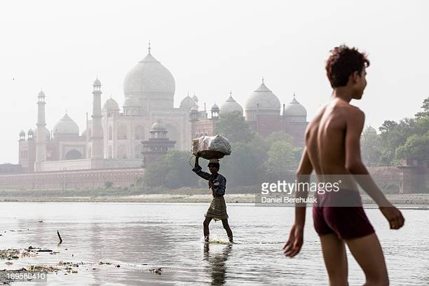 An Indian man carries goods as crosses the Yamuna river with the Taj Mahal is seen in the distance on May 28 2013 in Agra India Completed in 1643 the...