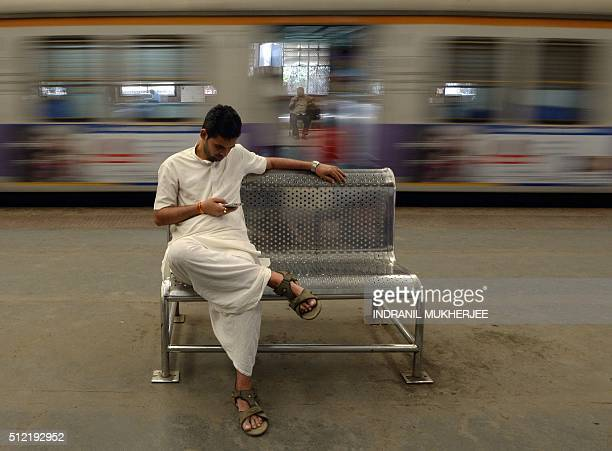 An Indian man checks his mobile phone as a suburban train leaves a station in Mumbai on February 25 2016 Indian Railway minister Suresh Prabhu...