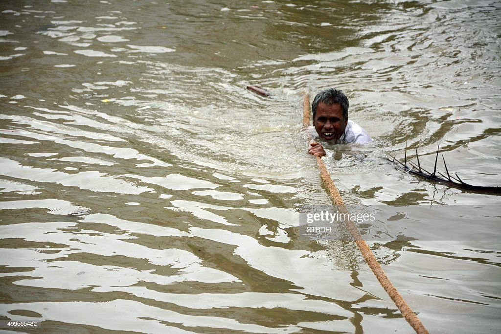 TOPSHOT An Indian man clings to a rope as he makes his way through floodwaters in Chennai on December 2 2015 India has deployed troops to Tamil Nadu...