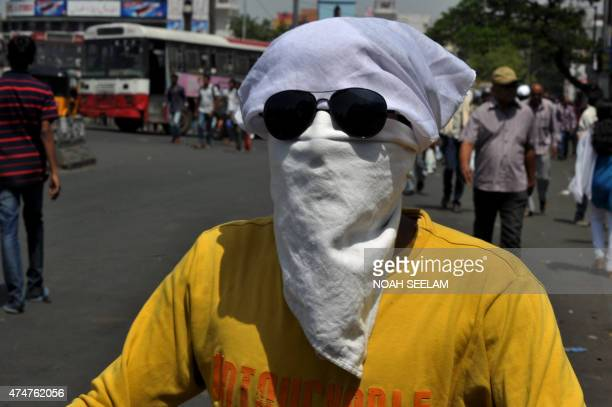 An Indian man covers his face as drives on a scooter under the hot sun in Hyderabad on May 26 2015 More than 430 people have died in two Indian...