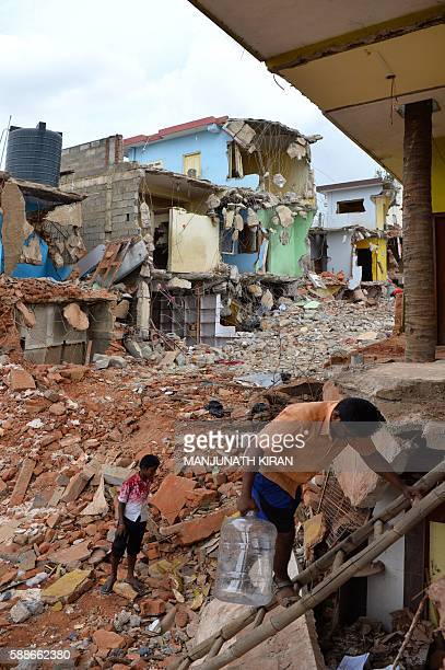 An Indian man descends on a ladder amidst the debris of demolished houses a day after Bangalore's municipal authority Bruhat Bengaluru Mahanagara...