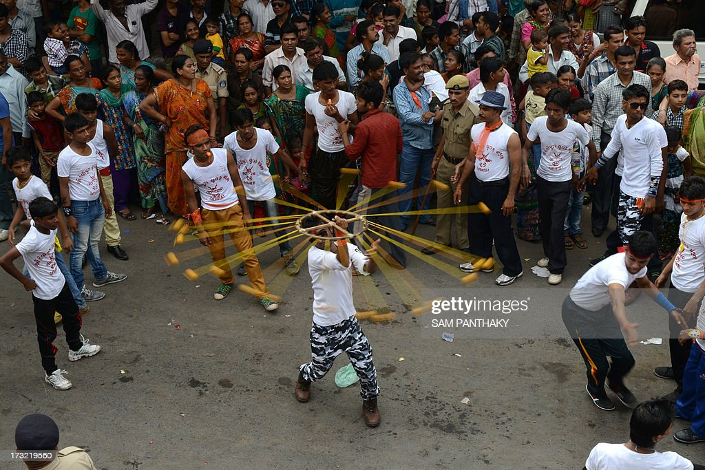 An Indian man displays his skills as Hindu devotees watch during the 136th Lord Jagannath Rath Yatra in Ahmedabad on July 10, 2013. According to mythology, the Rath Yatra dates back some 5,000 years when Hindu god Krishna, along with his older brother Balaram and sister Subhadra, were pulled on a chariot from Kurukshetra to Vrindavana by Krishna's devotees. AFP PHOTO / Sam PANTHAKY