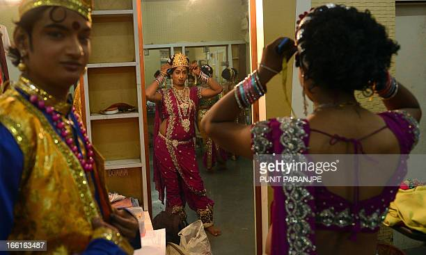 An Indian man dressed as a female looks in the mirror as he prepares for the 'Lavani' performance in Mumbai on April 8 2013 Lavani is a genre of...
