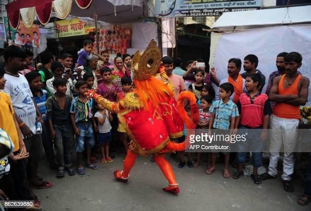 An Indian man dressed as Hindu monkey god Hanuman blesses bystanders as he participates in a procession for the Hindu festival Hanuman Jayanti in...