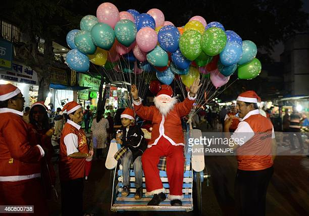 An Indian man dressed as Santa Claus takes part in a Christmas carnival procession in Mumbai on December 23 2014 Despite Christians forming a little...
