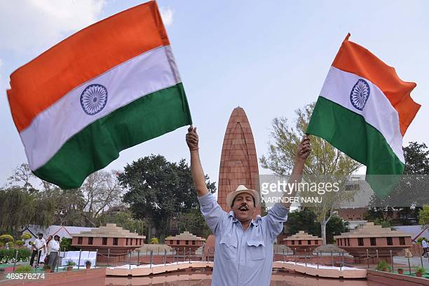 An Indian man dressed as the freedom fighter Bhagat Singh waves Indian national flags on the 96th anniversary of the Jallianwala Bagh massacre at the...