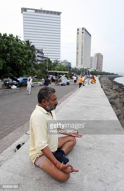 An Indian man exercises as others walk on Marine Drive in Mumbai early November 30 close to The Oberoi Hotel one of the sites of attacks by militant...