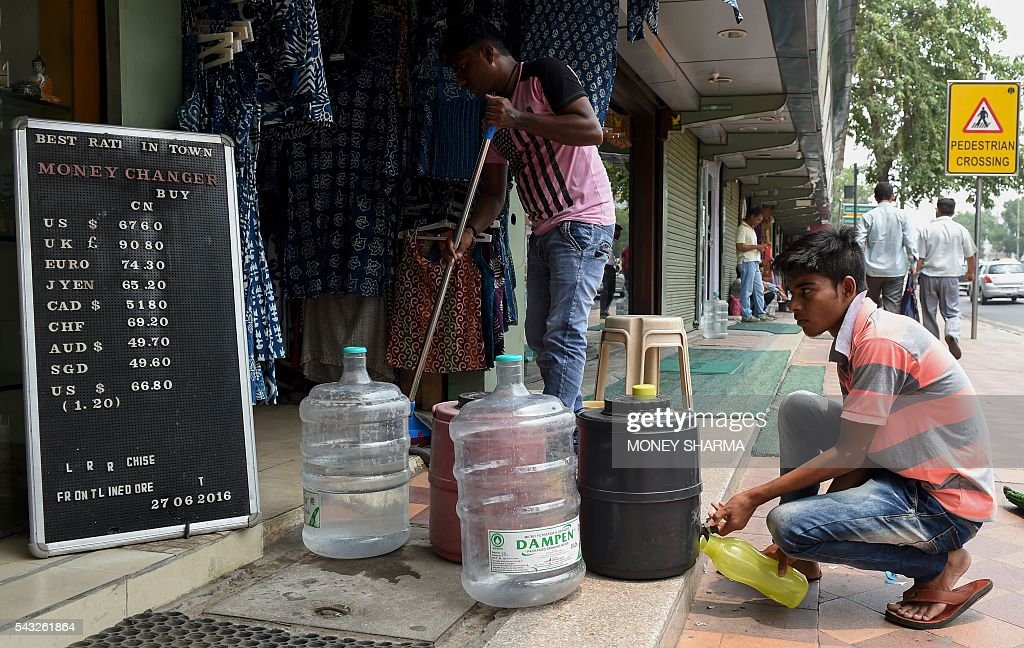 An Indian man fills a water bottle next to a board displaying currency exchange rates outside a shop in New Delhi on June 27, 2016. The pound sank on June 27 to 30-year lows while most stock markets tumbled following Britain's decision to leave the European Union, with traders fearing it will lead to months of uncertainty. / AFP / MONEY