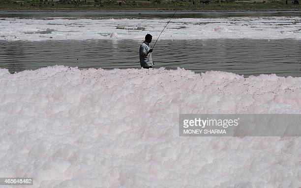An Indian man fishes on the banks of the polluted river Yamuna in New Delhi on March 9 2015 Despite being heavily polluted and laden with sewage...