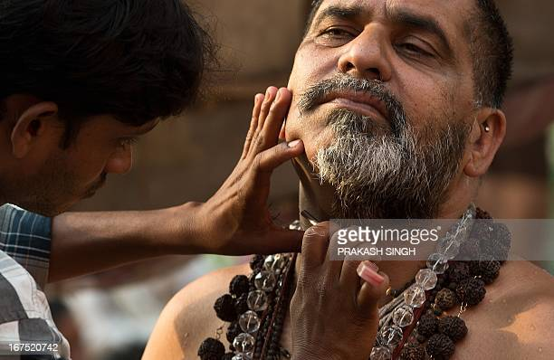 An Indian man gets shaved on the banks of Ganges river in Varanasi on April 26 2013 Varanasi is a city on the banks of the Ganges in Uttar Pradesh...